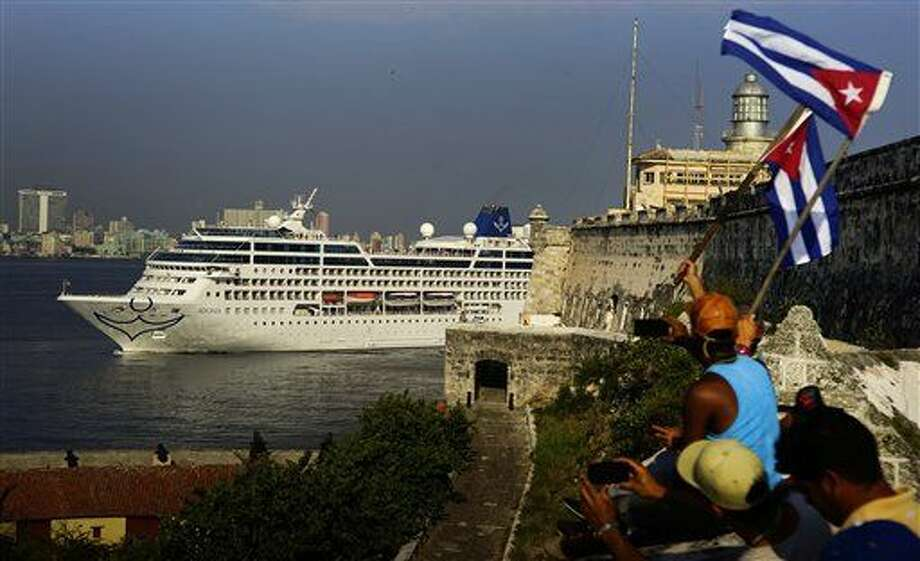 People waving Cuban flags greet passengers on Carnival's Adonia cruise ship as they arrive from Miami in Havana, Cuba, Monday, May 2, 2016. The Adonia's arrival is the first step toward a future in which thousands of ships a year could cross the Florida Straits, long closed to most U.S.-Cuba traffic due to tensions that once brought the world to the brink of nuclear war. (AP Photo/Ramon Espinosa) Photo: Ramon Espinosa