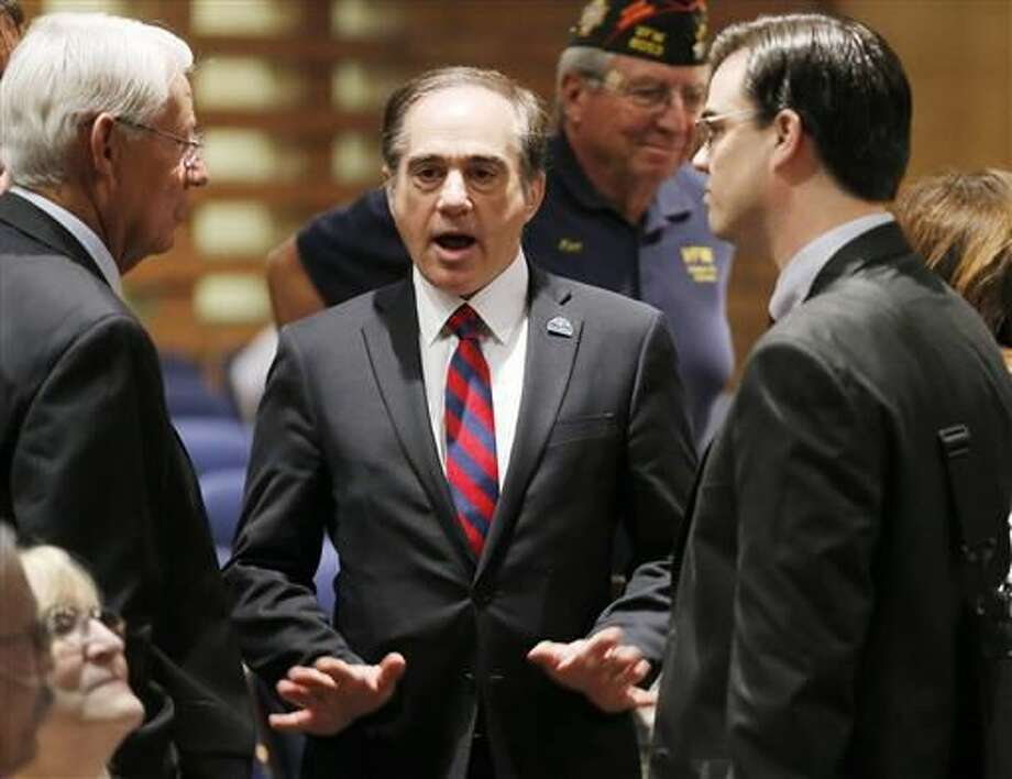 FILE - In this Dec. 14, 2015, file photo, U.S. Department of Veterans Affairs for Health Undersecretary Dr. David Shulkin, center, talks with attendees prior to testifying about the current state of the VA Medical Center in Phoenix at a Senate Veterans' Affairs Committee field hearing in Gilbert, Ariz. The Department of Veterans Affairs says that an average of 20 veterans a day committed suicide in 2014, a slight decrease from a previous government estimate for 2010. Shulkin told The Associated Press that the data used for the latest suicide projections came from every state and U.S. territory and was the largest analysis of veteran records ever undertaken by the department. (AP Photo/Ross D. Franklin, File) Photo: AP Photo/Ross D. Franklin,  File