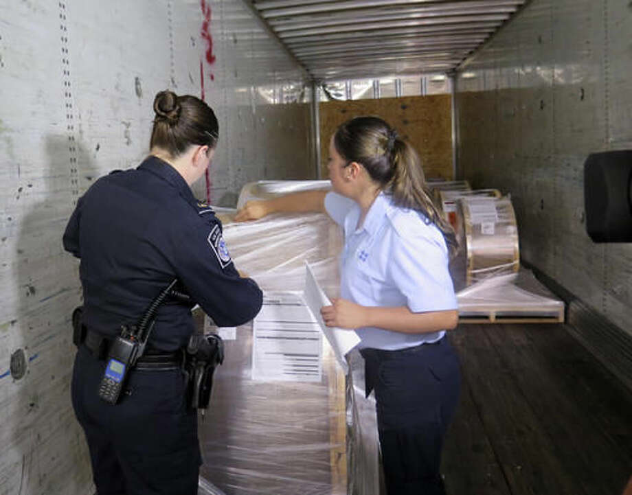 U.S. Customs and Border Protection officer Rachel McCormick, left, and Mexican customs officer Alejandra Galindo demonstrate how they would jointly inspect a cargo truck carrying goods from Mexico into the U.S. while at the Mariposa Inspection Facility at the Nogales Port of Entry in Arizona. Officials say the new program allowing Mexican officials to work with their U.S. counterparts has already reduced wait times by more than 75 percent. (AP Photo/Astrid Galv'n) Photo: Astrid Galv'n