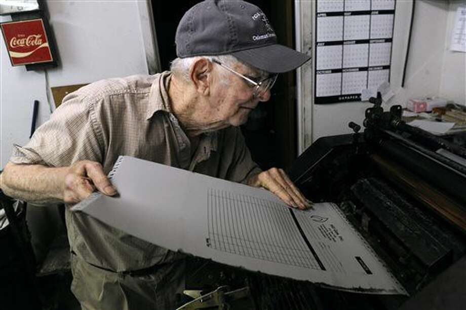 "ADVANCE FOR MONDAY, AUG. 8 AND THEREAFTER - In a Wednesday July 27, 2016 photo, Odell ""Woody"" Ormsby, 88, loads a plate onto a printing press at the Comanche Chief in Comanche, Texas. Ormsby has worked in the newspaper's print shop for 70 years and while the newspaper itself is printed elsewhere, the commercial printing jobs are still handled in-house. The Chief is Comanche County's oldest business, its first issue was published August 21, 1873. (Ronald W. Erdrich/Abilene Reporter-News via AP) Photo: Ronald W. Erdrich"