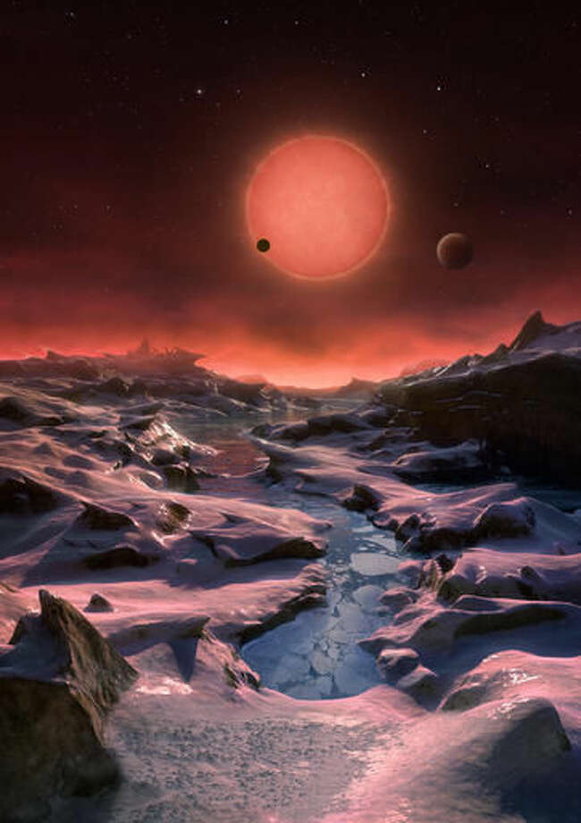 The artist's impression provided by European Southern Observatory on May 2, 2016 shows an imagined view from the surface one of the three planets orbiting an ultracool dwarf star just 40 light-years from Earth that were discovered using the TRAPPIST telescope at ESO's La Silla Observatory. (ESO/M. Kornmesser via AP) MANDATORY CREDIT Photo: M. Kornmesser