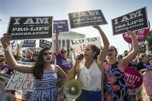 Reagan Barklage of St. Louis, center, and other anti-abortion activists demonstrate in front of the Supreme Court in Washington, Monday, June 27, 2016, as the justices struck down the strict Texas anti-abortion restriction law known as HB2. The justices voted 5-3 in favor of Texas clinics that had argued the regulations were a thinly veiled attempt to make it harder for women to get an abortion in the nation's second-most populous state. (AP Photo/J. Scott Applewhite)