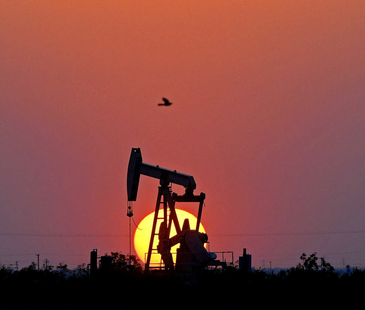 The sun sets behind a pumpjack on Highway 191 in Midland County, Thursday, April 28, 2016. James Durbin/Reporter-Telegram