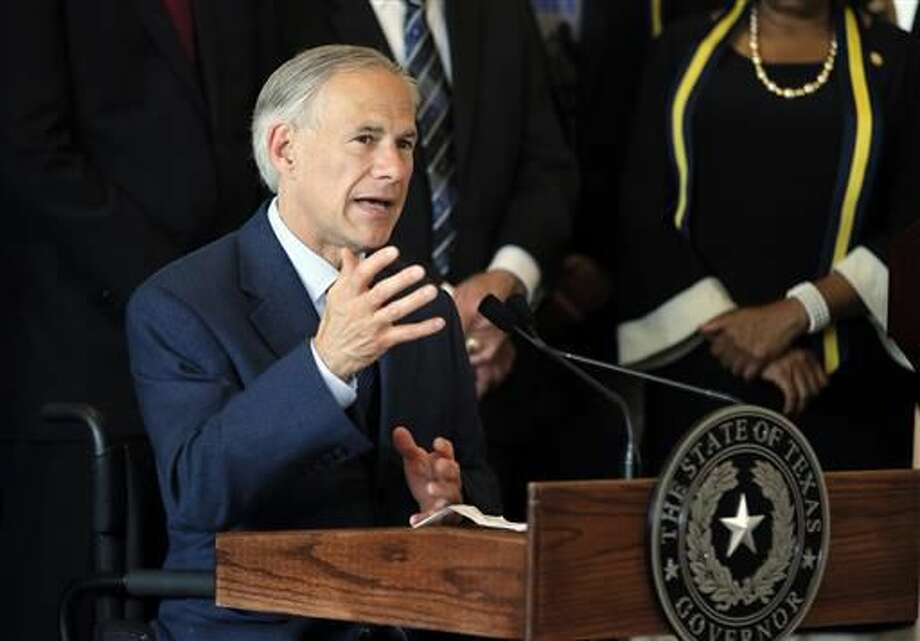 FILE - In this Friday, July 8, 2016 file photo, Texas Gov. Greg Abbott, right, responds to questions about the police shootings during a news conference at City Hall in Dallas.  (AP Photo/Tony Gutierrez, File)