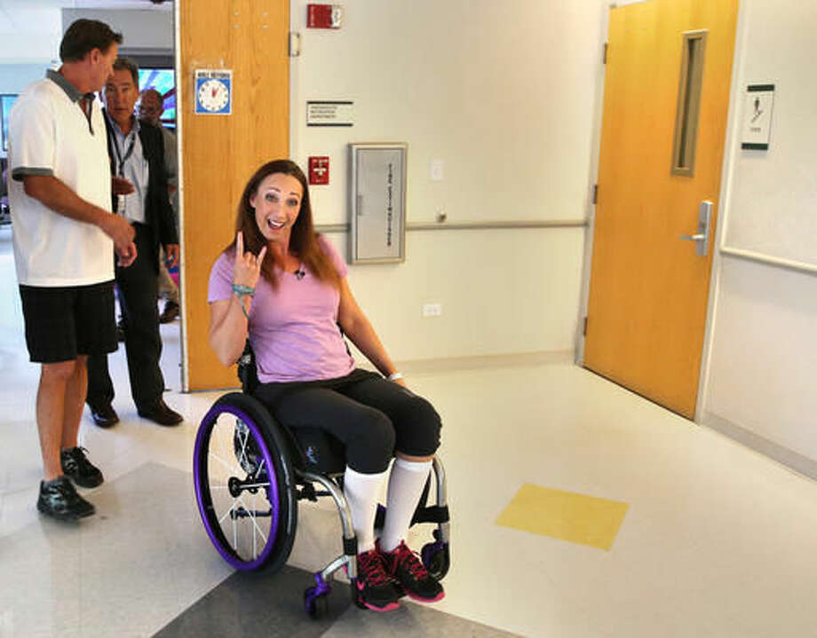 """FILE - In this Aug. 14, 2014, file photo, AmyVanDyken-Rouen gestures as she leaves Craig Hospital with her husband, Tom Rouen, left, in Englewood, Colo. In an Instagram post on June 8, 2016, Van Dyken-Rouen said she was referred to as a """"cripple"""" by an employee at a Texas hotel. She later wrote on Twitter that the hotel's general manager apologized. (AP Photo/Brennan Linsley, File) Photo: Brennan Linsley"""