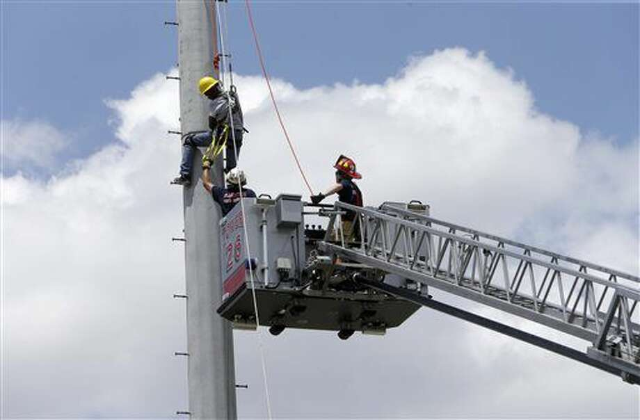 A worker climbs down a light tower at W.W. Thorne Stadium with help from firefighters Tuesday, Aug. 9, 2016, in Houston. Officials said the man was working on the lights when he became dizzy and needed help to get down. Firefighters put a harness and ropes on the man to assist him down the light tower. ( Melissa Phillip/Houston Chronicle via AP) Photo: Melissa Phillip