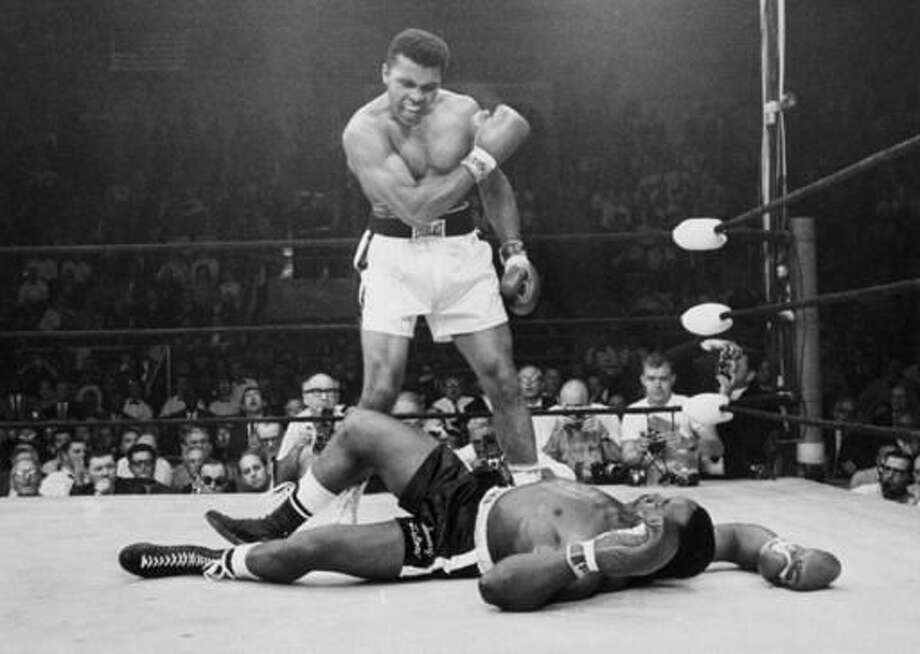 FILE - In this May 25, 1965, file photo, heavyweight champion Muhammad Ali, then known as Cassius Clay, stands over challenger Sonny Liston, shouting and gesturing shortly after dropping Liston with a short hard right to the jaw, in Lewiston, Maine. Ali, the magnificent heavyweight champion whose fast fists and irrepressible personality transcended sports and captivated the world, has died according to a statement released by his family Friday, June 3, 2016. He was 74. (AP Photo/John Rooney, File) Photo: JOHN ROONEY