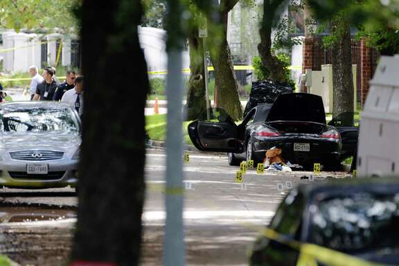 Police investigate the suspect's car in Monday morning's shooting along Law Street at Weslayan, September 26, 2016.