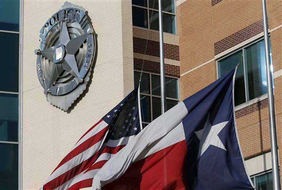 The American and Texas flag sit at half-staff outside of the Dallas police department headquarters, Friday, July 8, 2016, in Dallas. Five law enforcement officers were killed with several more injured by a suspected lone gunman after a planned rally Thursday night. (AP Photo/Tony Gutierrez) Photo: Associated Press