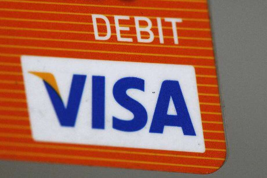 FILE - This Aug. 16, 2010 file photo shows the Visa logo on the front of a Debit Card in Philadelphia. Visa reports quarterly financial results on Wednesday, Oct. 29, 2014. (AP Photo/Matt Rourke, File)