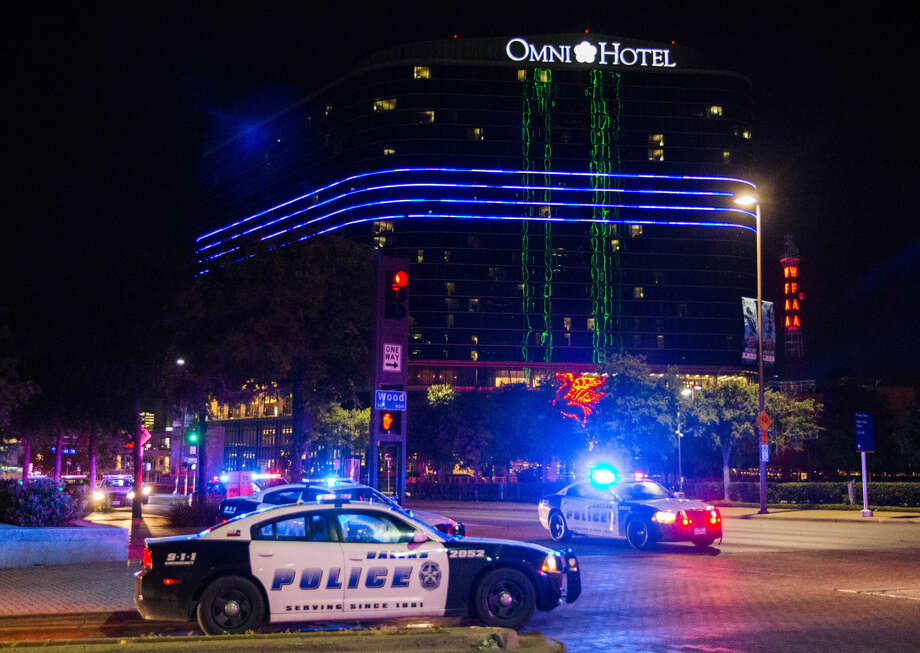 The Omni Hotel displays a blue stripe over police vehicles to show solidarity with Dallas police on Thursday, July 7, 2016 in Dallas. Snipers opened fire on police officers in the heart of Dallas during protests over two recent fatal police shootings of black men. (Ashley Landis/The Dallas Morning News via AP) Photo: Ashley Landis