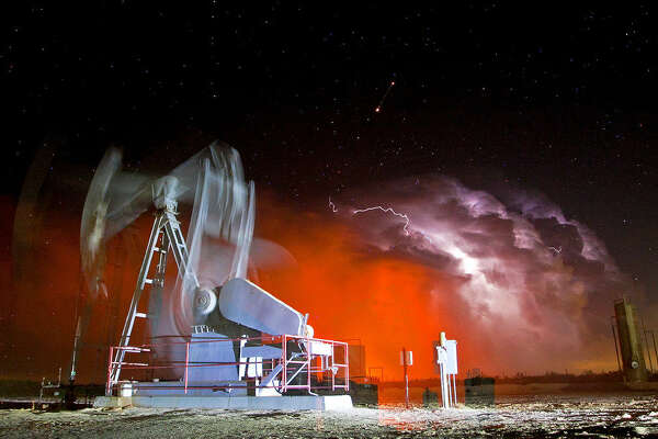 A natural gas flare colors the sky orange as a bolt of lightning strikes through the clouds near a pumpjack located by Highway 349 north of the Midland County line Saturday, May 28, 2016. James Durbin/Reporter-Tele­gram