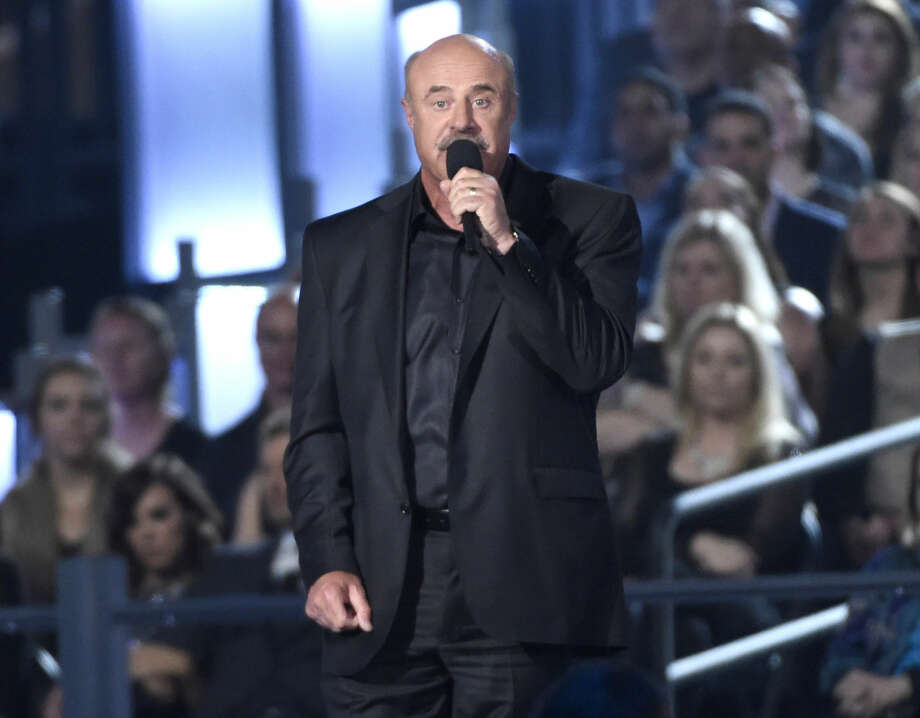 FILE - In a Sunday, April 19, 2015 file photo, Dr. Phil McGraw speaks on stage at the 50th annual Academy of Country Music Awards at AT&T Stadium, in Arlington, Texas. McGraw and The National Enquirer are lining up for a courtroom brawl after the television talk show host and his wife filed a $250 million lawsuit against the supermarket tabloid and its sister publications, charging that they falsely accused him of being an abusive husband and a hypocrite who doesn't practice what he preaches. (Photo by Chris Pizzello/Invision/AP, File) Photo: Chris Pizzello