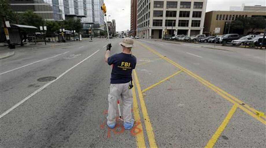 Investigators work in the area of downtown Dallas that remains an active crime scene, Saturday, July 9, 2016. Micah Johnson, an Army veteran, opened fire on police officers in the heart of Dallas Thursday, as hundreds of people were gathered to protest two recent fatal police shootings of black men, Philando Castile and Alton Sterling. Photo: Associated Press