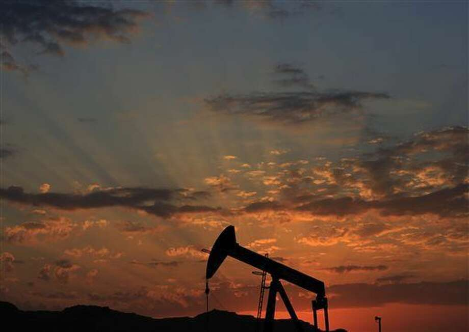 FILE - In this Dec. 13, 2015 file photo the sun sets behind an oil pump in the desert oil fields of Sakhir, Bahrain.Iran expects foreign oil companies to sign deals valued at $25 billion over the next one to two years under the terms of a new contract model approved last week. (AP Photo/Hasan Jamali, File)