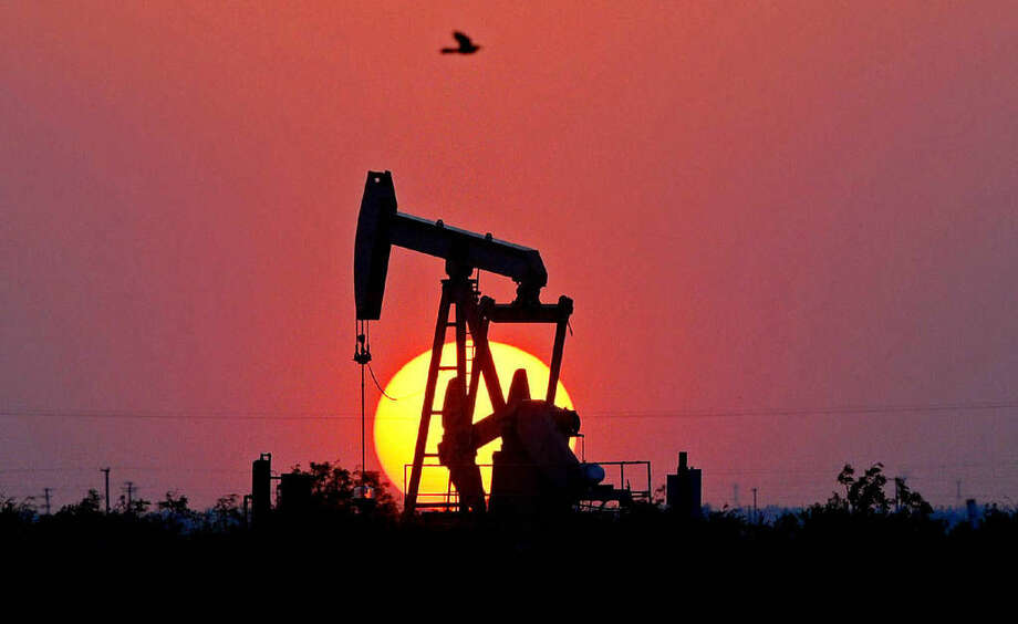 The sun sets behind a pumpjack on Highway191in Midland County, Thursday, April 28, 2016. James Durbin/Reporter-Telegram