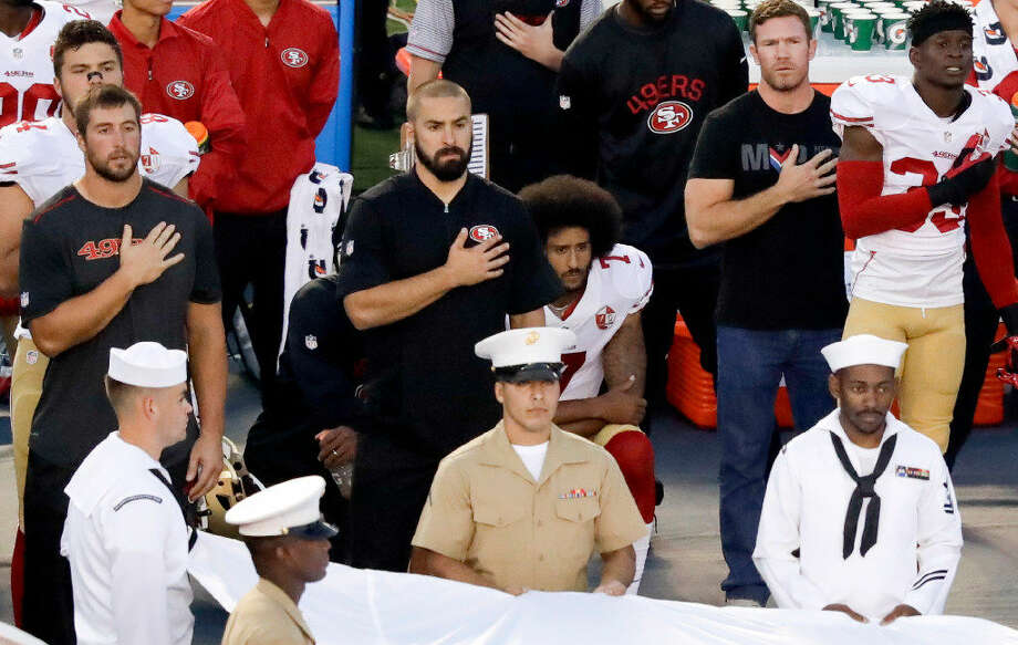 FILE - In this Thursday, Sept. 1, 2016, file photo, San Francisco 49ers quarterback Colin Kaepernick, center, kneels during the national anthem before an NFL preseason football game against the San Diego Chargers in San Diego. With Case Keenum and Blaine Gabbert set as starting quarterbacks, Kaepernick's refusal to stand for the anthem getting more public acceptance and the Rams mostly settled into their new home, much of the focus when the teams open the season on Monday night will be on the running backs. (AP Photo/Chris Carlson, File)
