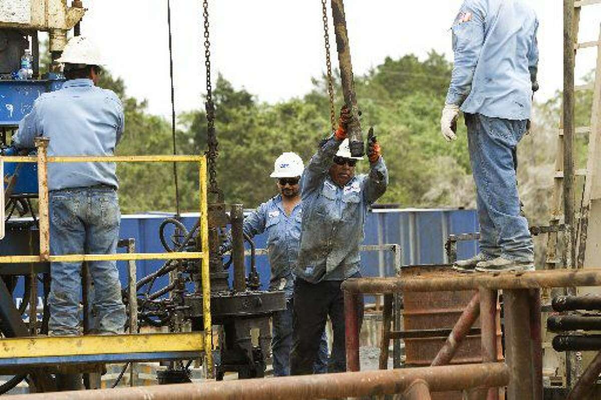 An oilfield worker for KeyEnergyServices, guilds a drill pipe from a well at an EnerVest oil field Tuesday, May 10, 2011, in rural Fayette County. ( Brett Coomer / Houston Chronicle )