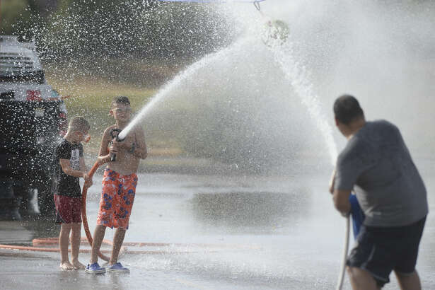 Event attendees compete to move a suspended ball with water hoses during the Midland Fire Department Wet 'n' Wild event on Wednesday, Aug. 10, 2016, at CJ Kelly Park. James Durbin/Reporter-Telegram