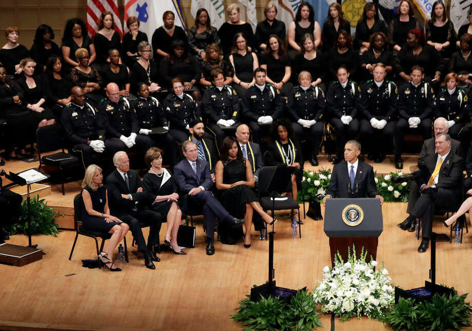 President Barack Obama, pauses while speaking during a memorial service at the Morton H. Meyerson Symphony Center, Tuesday, July 12, 2016, in Dallas, for five police officers were killed and several injured during a shooting in downtown Dallas last Thursday night. Seated, from left are, Jill Biden, Vice President Joe Biden, former first lady Laura Bush, former president George W. Bush, first lady Michelle Obama and Dallas Mayor Mike Rawlings. (AP Photo/Eric Gay)