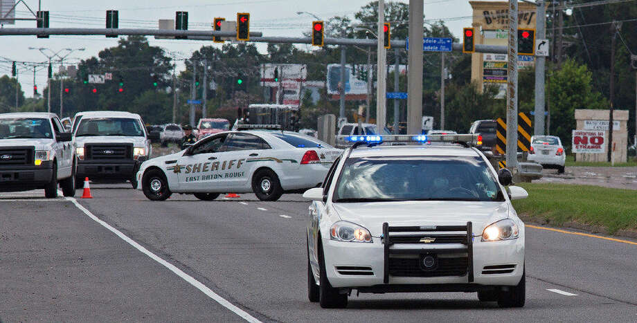 Baton Rouge Police arrive at the scene on Airline Highway after police were shot in Baton Rouge, La., Sunday, July 17, 2016. At least three officers are confirmed dead and at least three others wounded after the shooting, a sheriff's office spokeswoman said Sunday. One suspect is dead and law enforcement officials believe two others are still at large, the spokeswoman said. (AP Photo/Max Becherer)