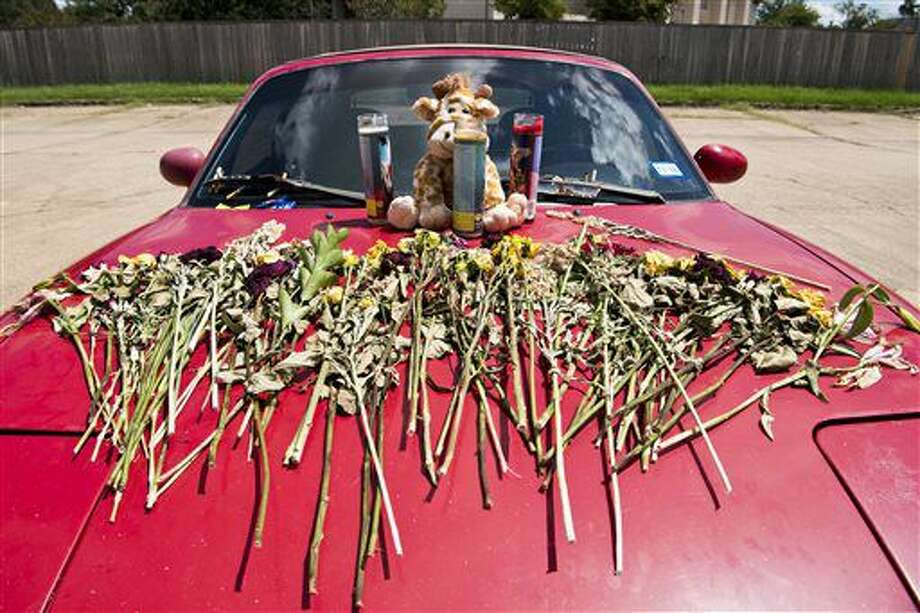 A memorial of flowers, candles and a stuffed animal sit on the hood of a car in front of the Sigma Nu fraternity house in College Station in August. A student died of a drug overdose after attending a fraternity party.  Photo: Timothy Hurst