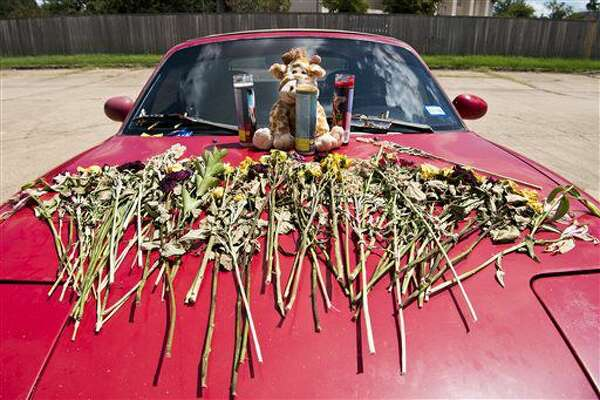 A memorial of flowers, candles and a stuffed animal sit on the hood of a car in front of the Sigma Nu fraternity house in College Station, Texas, Wednesday, Aug. 24, 2016. Authorities have identified a Texas A&M University student who investigators believe died of a drug overdose after being found unresponsive Saturday at a fraternity house as Anton Gridnev. (Timothy Hurst/College Station Eagle via AP)