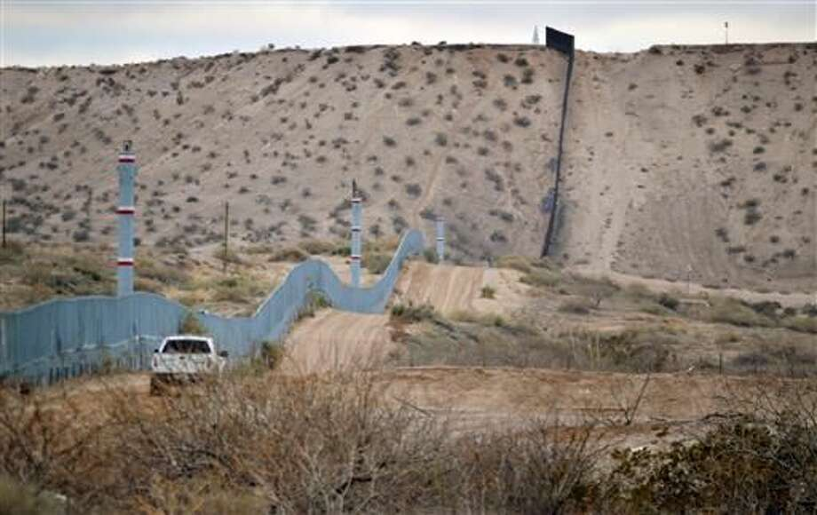 FILE - In this Jan. 4, 2016 file photo, a U.S. Border Patrol agent drives near the U.S.-Mexico border fence in Sunland Park, N.M. A new Cronkite News-Univision News-Dallas Morning News Border Poll released Monday, July 18, 2016, says a majority of residents surveyed on both sides of the U.S.-Mexico border are against the building of a wall between the two countries. The poll also suggests residents feel Democrats and Republicans are ignoring their concerns and aren't proposing solutions to help their economy and combat drug trafficking and human smuggling. (AP Photo/Russell Contreras, File)
