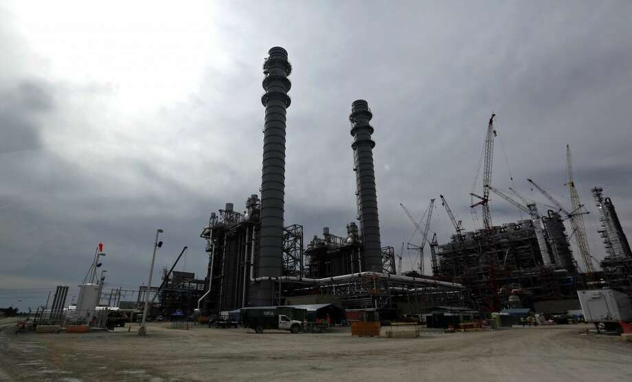 In this Oct. 21, 2013 photo, the H2S and CO2 absorber vessels are shown in silhouette at the Mississippi Power's Kemper County energy facility in central Mississippi near DeKalb. Construction continues at the power plant that is designed to use a soft form of coal called lignite in a gasification process to generate power. The plant, America's newest, most expensive coal-fired power plant is hailed as one of the cleanest on the planet, thanks to government-backed technology that removes carbon dioxide and keeps it out of the atmosphere. Once the carbon is stripped away, it will be used to do something that is not so green at all – extract oil. Power companies sell the carbon dioxide to oil companies, which pump it into old oil fields to force more crude to the surface. (AP Photo/Rogelio V. Solis)  Photo: Rogelio V. Solis