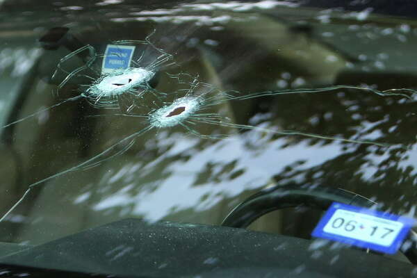 Bullet holes in the windshield of Alan Wakim's Mustang at the scene of a shooting along Wesleyan at Law Street that left at least nine people injured and the alleged shooter dead, Sunday morning, Sept. 25, 2016, in Houston.