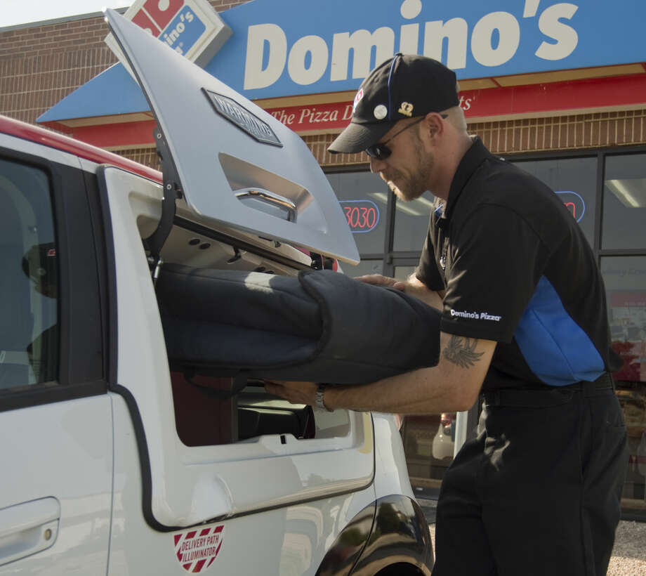 Chris McDougle, supervisor, demonstrates the pizza warming box in Domino's Pizza new DXP delivery cars Tuesday 07-12-16. Tim Fischer/Reporter-Telegram Photo: Tim Fischer