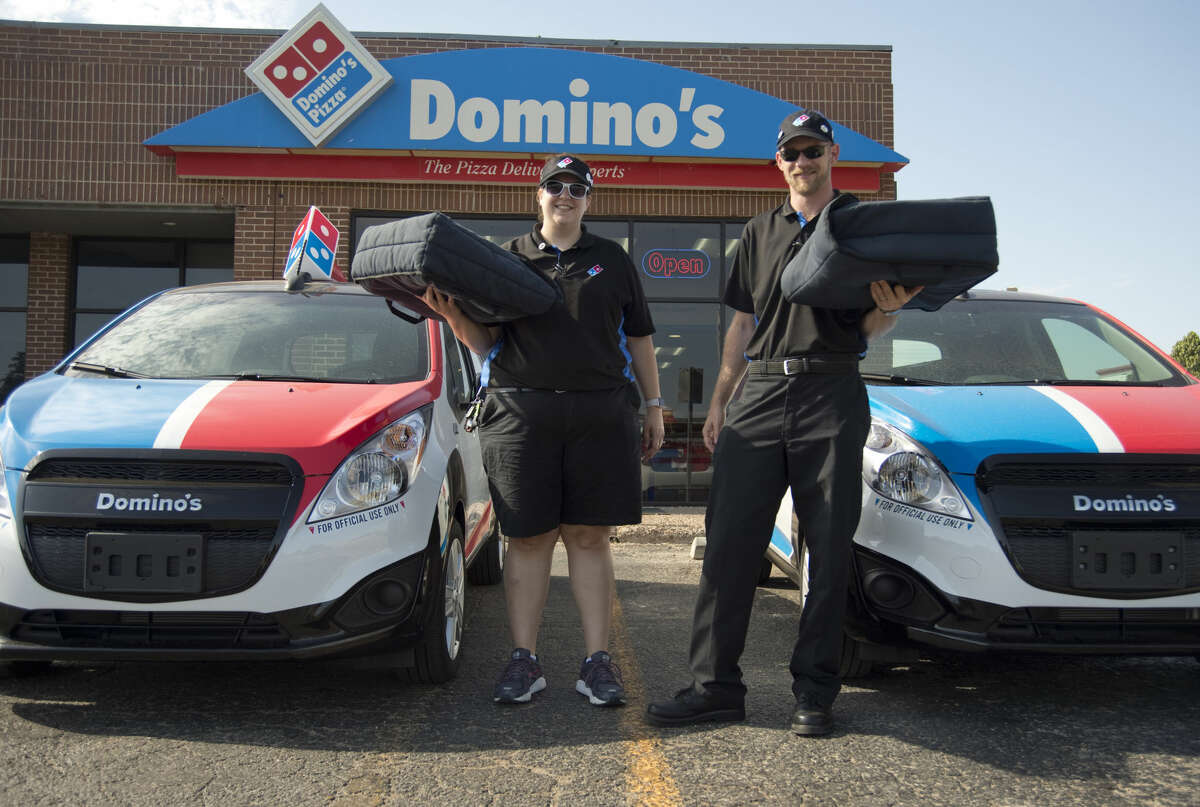 Renee McDougle, Domino's event coordinator and her husband Chris McDougle, supervisor, show off the two new DXP delivery cars Tuesday 07-12-16. Tim Fischer/Reporter-Telegram
