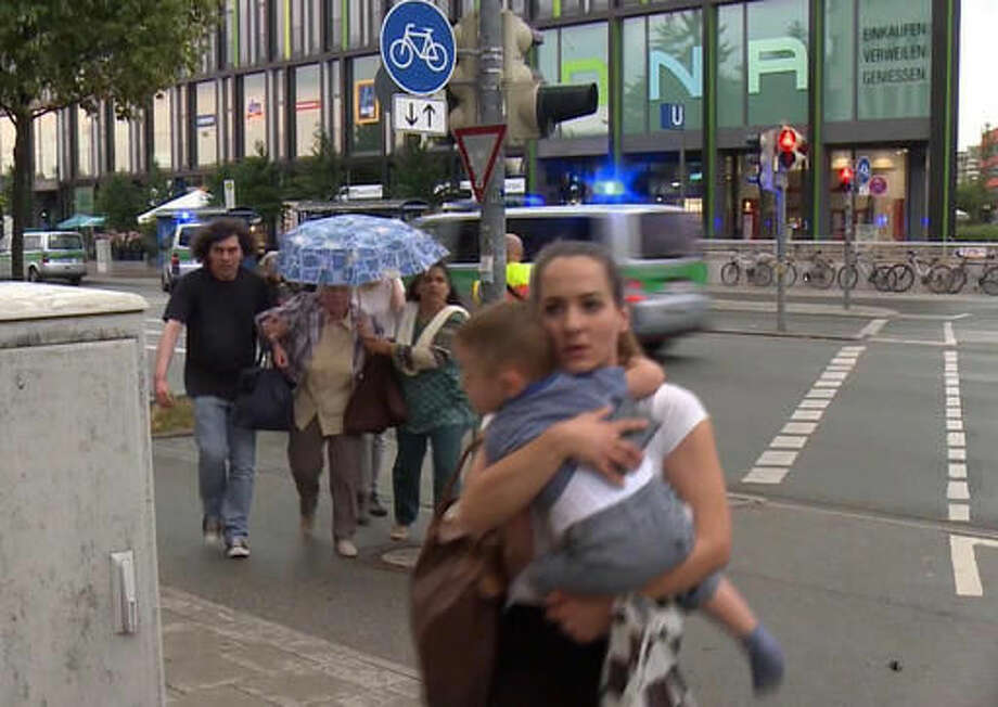 Members of the public run away from the Olympia Einkaufszentrum mall, after a shooting, in Munich, Germany, Friday, July 22, 2016. A manhunt was underway Friday for a shooter or shooters who opened fire at a shopping mall in Munich, killing and wounding several people, a Munich police spokeswoman said. The city transit system shut down and police asked people to avoid public places. (AP) Photo: TEL