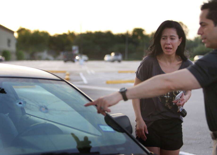 Alan Wakim shows his wife, Jennifer Molleda, where two bullets entered his windshield and went past his face during a shooting along Wesleyan at Law Street that left at least nine people injured and the alleged shooter dead, Sunday morning, Sept. 25, 2016, in Houston. ( Mark Mulligan / Houston Chronicle ) Photo: Mark Mulligan/Houston Chronicle
