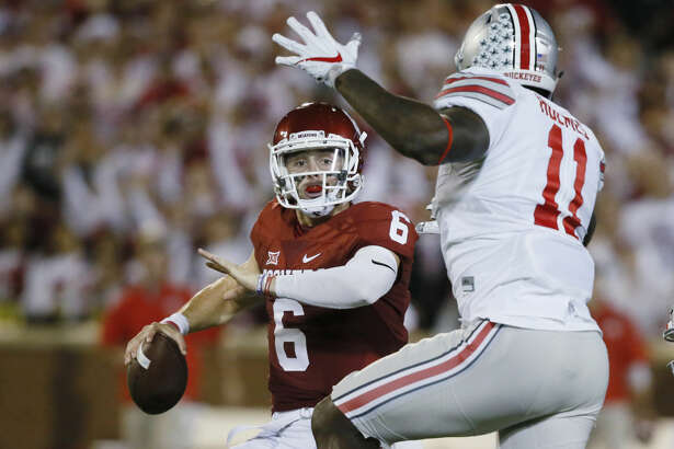 Oklahoma quarterback Baker Mayfield (6) is pressured by Ohio State defensive end Jalyn Holmes (11) during an NCAA college football game between Ohio State and Oklahoma in Norman, Okla., Saturday, Sept. 17, 2016. (AP Photo/Sue Ogrocki)