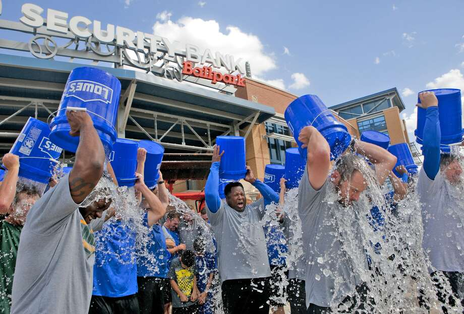 A group of Rockhounds team and office staff as well as two Midland police officers and a city councilman participate in the ice bucket challenge to raise awareness for amyotrophic lateral sclerosis (ALS), also known as Lou Gehrig's disease on Wednesday at Security Bank Ballpark. James Durbin/Reporter-Telegram