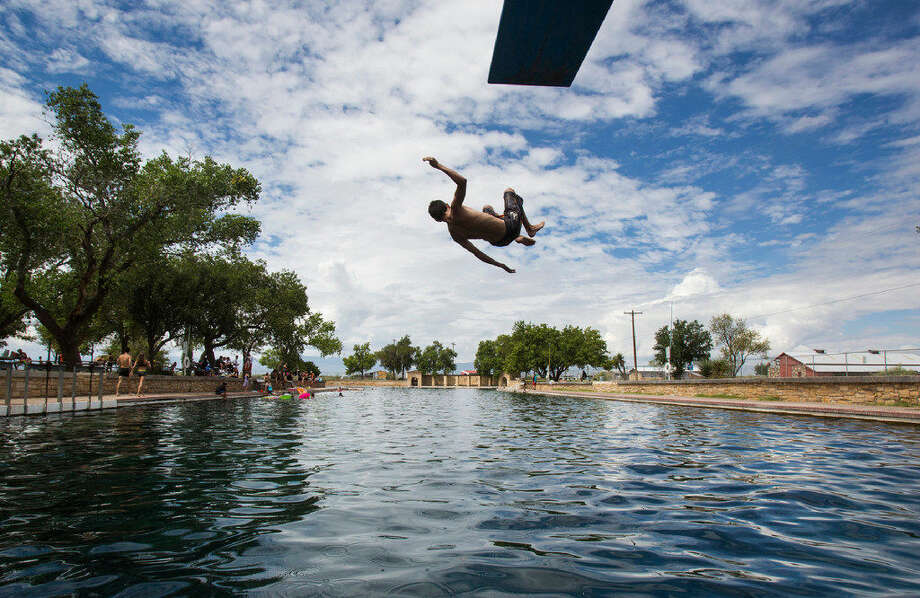 A In this Aug. 18, 2016 photo, a boy jumps off the diving board into 30 feet of water at the natural spring pool at the Balmoreah State Park in Balmoreah, Texas. The rise of fracking nearby the town has some community members worried about their drinking water and natural springs, which serve as a popular tourism destination helping drive the town's economy.  Photo: (Brittany Greeson/The San Antonio Express-News)