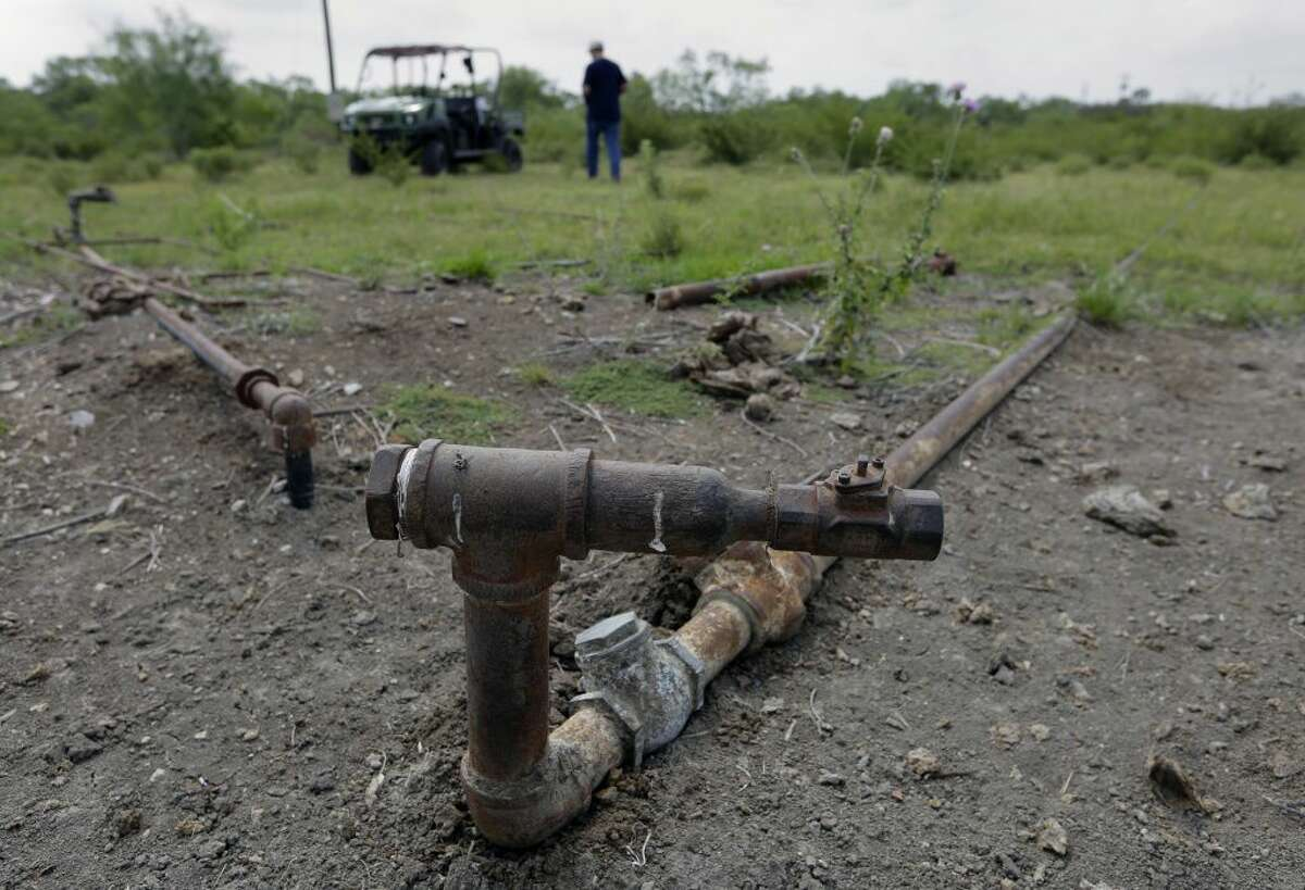 Parts of an injection well used to pump oil sits idle on a South Texas ranch near Bigfoot. Deserted drilling wells are the relics of every oil bust, and Texas is pitted with more than any other place in the U.S.