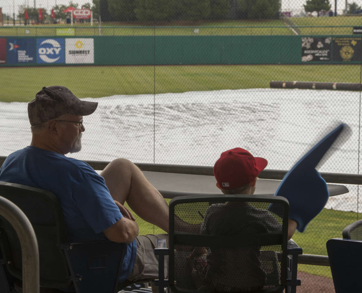 John Howard and his grandson Kasen Goodman, with other RockHounds fans and Texas Rangers fans hoping to see pitcher Colby Lewis, with Frisco for a rehab game, try to stay dry as the game time continues to be pushed back Monday 08-29-16 at Security Bank Ballpark. Tim Fischer/Reporter-Telegram