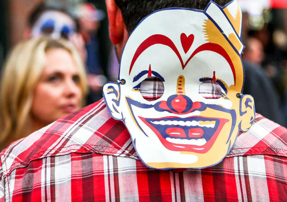 A carnival goer rests his paper clown mask on the back of his neck outside of the beer gardens at the Georgetown Carnival on June 11, 2016. (Lacey Young, seattlepi.com)