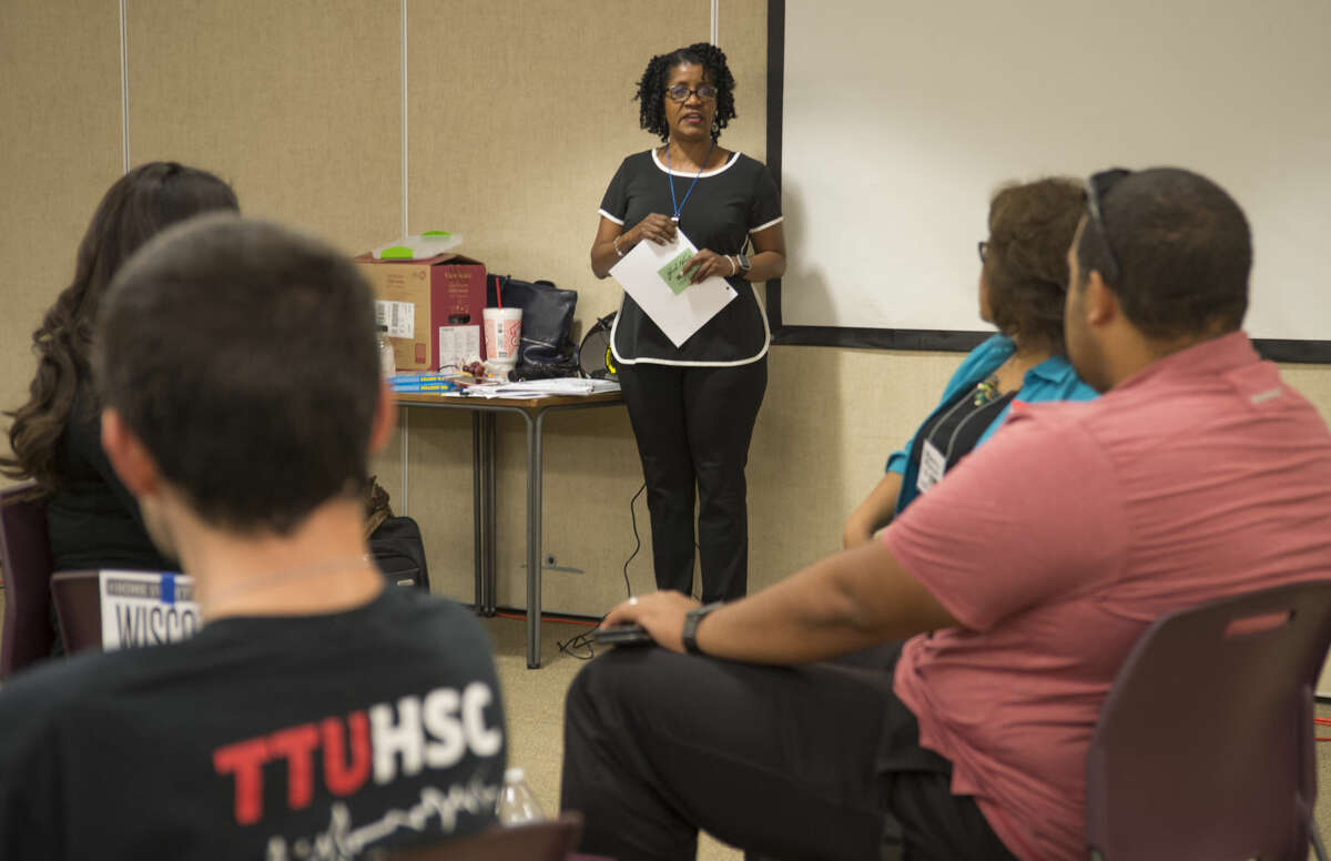 """Sharon Owens, facilitator, talks with area agency employees about the Poverty Simulation course Thursday 08-25-16 at Golf Course Road Church of Christ to help understand and """"live"""" a month in the life of a family living in poverty and learning what community resources are available in the area. Tim Fischer/Reporter-Telegram"""