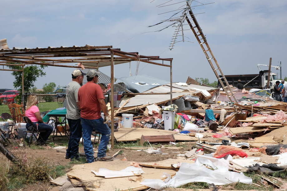 Neighbors, family members and friends look on at the wreckage of Delia Pierson's mobile home, which was completely destroyed by a tornado that occurred Sunday night in Glasscock County.  Photo: Erin Stone