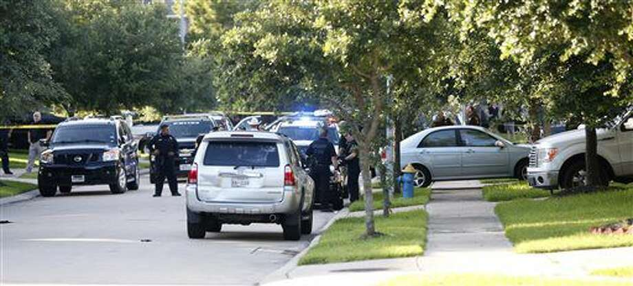 In this Friday, June 24, 2016 photo, Fort Bend County Sheriffs department investigate a shooting at Blanchard Grove and Remson Hollow in Katy, Texas. Officials said a woman shot her two adult daughters - killing one of them at the scene - before she was fatally shot by a responding police officer. (Karen Warren/Houston Chronicle via AP) Photo: Karen Warren