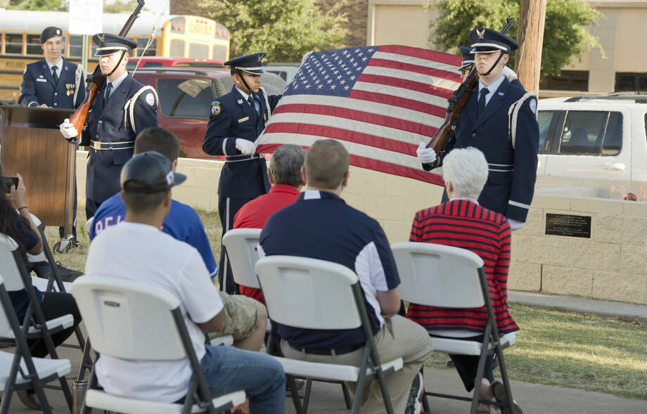 Midland High JrROTC honor guard members, Cadet Airman Basic Jacob Litavec, Cadet Tech Sgt. Robert Guevara, Cadet 2nd Lt. Thomas Pylant and Cadet Sr. Airman Francis Biggar present the flag to be retired Friday 05-27-16 in the new burnpit built as an Eagle Scout project by Cadet 2nd Lt. Garrett Hilliard, at podium, outside the MHS JrROTC building. Tim Fischer\Reporter-Telegram Photo: Tim Fischer