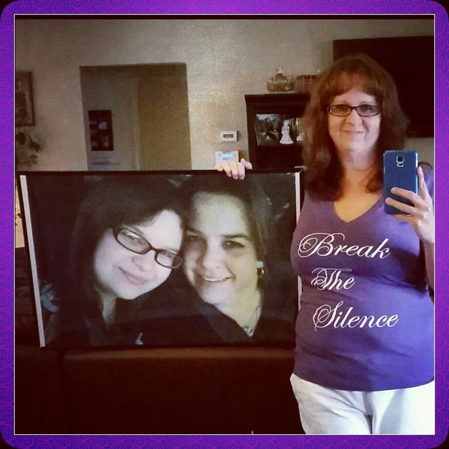 Laura Dimery holds a picture of her sister Jennifer Krieger and niece Kelsie who were both murdered by Krieger's fiance in 2013. Photo: Courtesy Photo