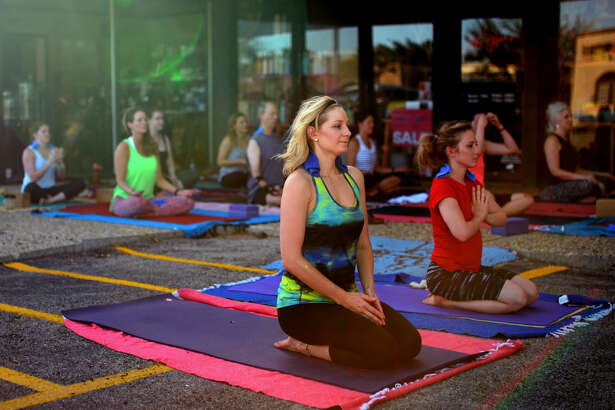 Free yoga class led by Cyndi Simpson in observance of International Yoga Day outside Midland Yoga Works on Tuesday, June 21, 2016. James Durbin/Reporter-Telegram