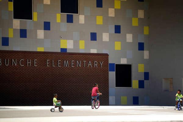 Children ride bikes past Bunche Elementary, closed for the summer, Saturday, July 23, 2016. James Durbin/Reporter-Telegram