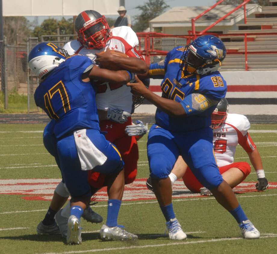 Wayland Baptist's Michael Nealy, 17, and Johnathan Slade, 95, wrap up a ballcarrier during a game earlier this season. The Pioneers knocked off No. 25-ranked Webber International (Fla.) Saturday, 31-20. Photo: Skip Leon, Plainview Herald