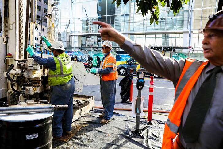 Construction workers Malakai Fakalolo (left), and Will Halai (center) use a Fraste machine while doing tests outside the Millennium Tower, a residential building which is leaning, in San Francisco, California, on Monday, Sept. 26, 2016. Engineer Patrick Shires (right) gives an interview.