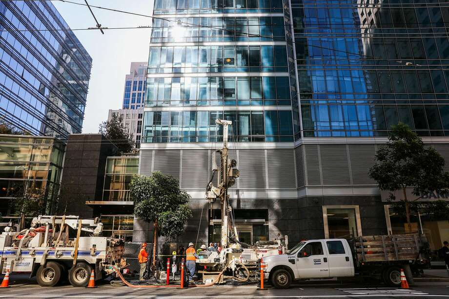 Workers test the soil outside Millennium Tower, the expensive residential high-rise at Mission and First streets that has begun to sink and tilt. Photo: Gabrielle Lurie, The Chronicle